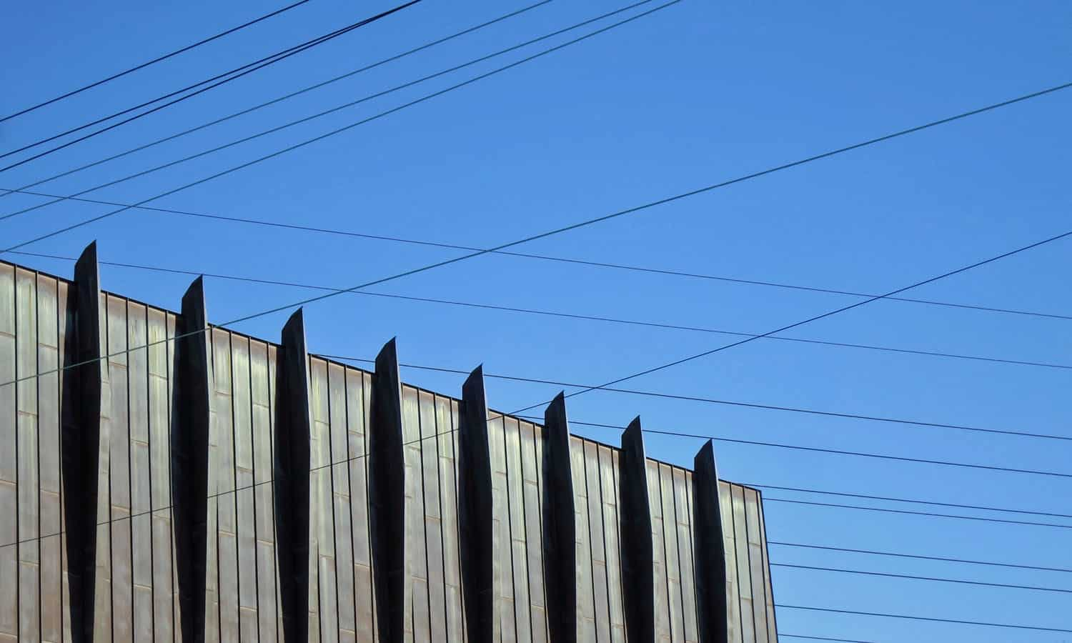 Amidst the hydro lines, the volume of the sanctuary is characterized by the rhythm of columns and the copper cladding