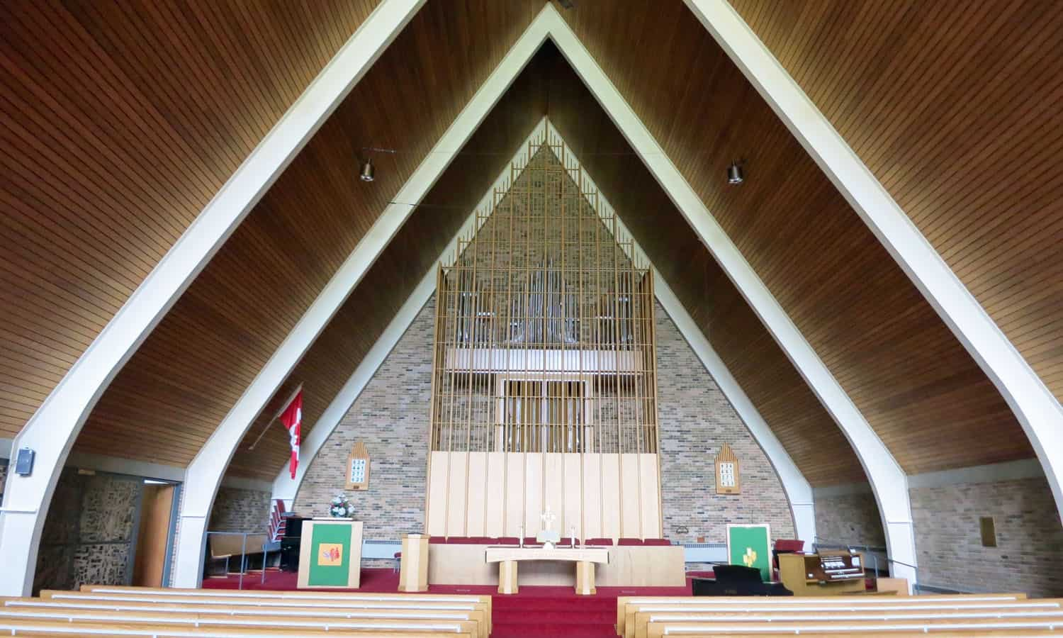 The interior of the sanctuary with its steel arches, wood ceiling, and brick walls and decorative organ screen